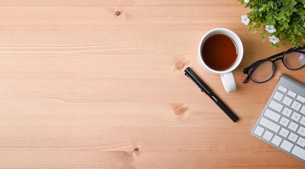 Кофейная чашка, клавиатура, очки и комнатное растение взгляда сверху на деревянной предпосылке взгляд сверху.