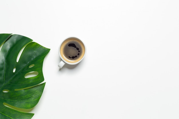 Top view of coffee cup and monstera leaf