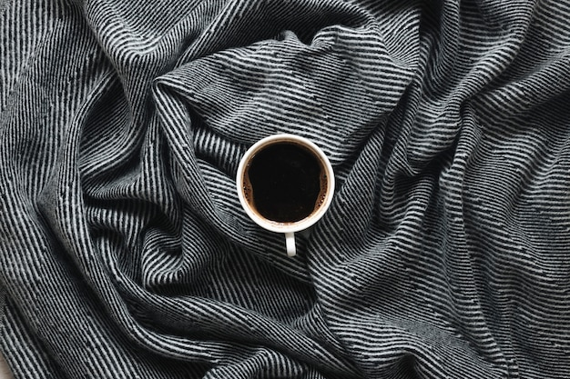 Top view of a coffee cup on stripe pattern cloth