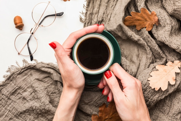 Top view of coffee cup with autumn leaves and blanket