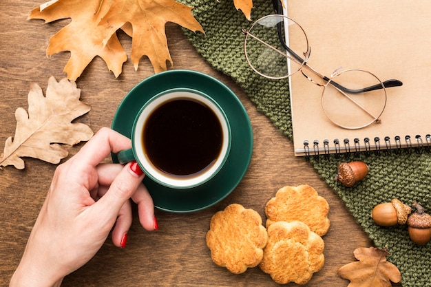 Top view of coffee cup with autumn leaves and notebook