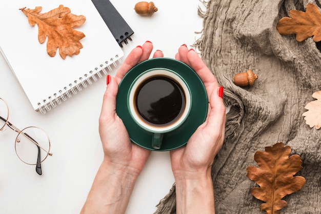 Top view of coffee cup with autumn leaves and notebooks