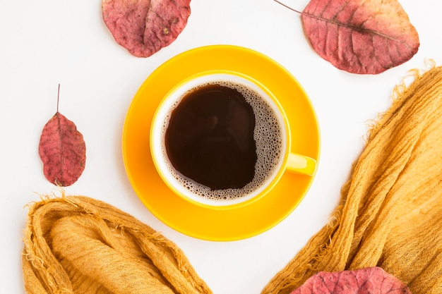 Top view of coffee cup with autumn leaves