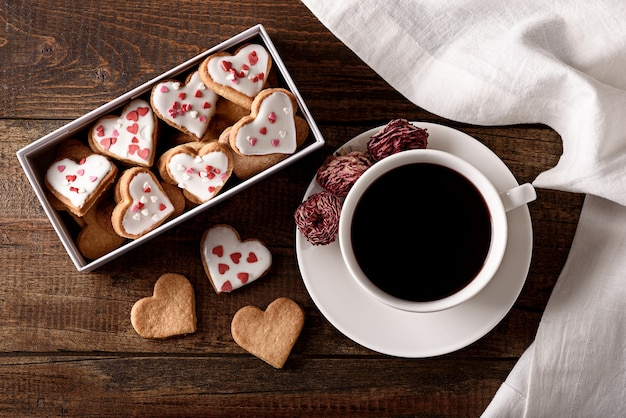 Top view coffee cup with box of glazed heart shaped cookies on brown wooden background
