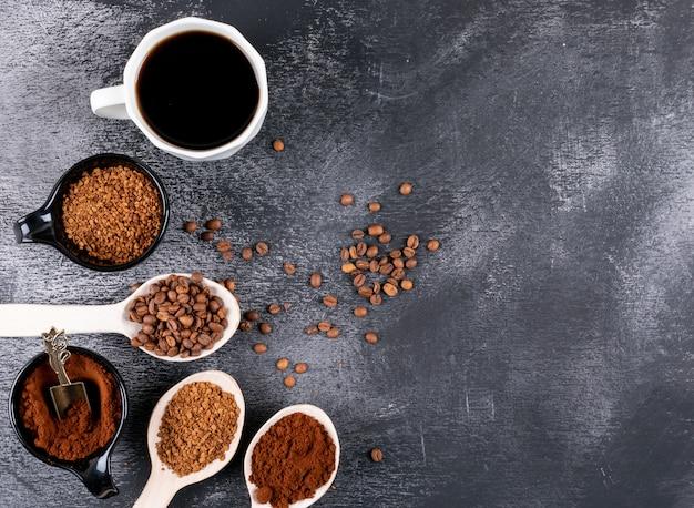 Вид сверху кофейная чашка с кофе в зернах и растворимый кофе на темном столе