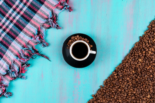 Top view coffee cup with coffee beans on blue table
