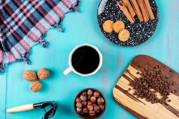 Tazza di caffè di vista superiore con i biscotti e i dadi dei chicchi di caffè sulla tavola blu