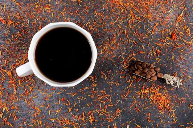 Top view coffee cup with coffee beans on dark table with spices