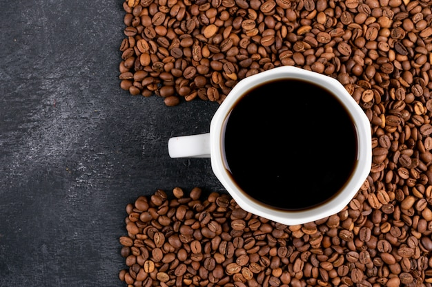 Top view coffee cup with coffee beans on dark table