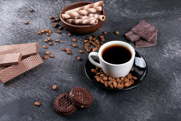 Top view coffee cup with coffee beans and different cookies on dark table