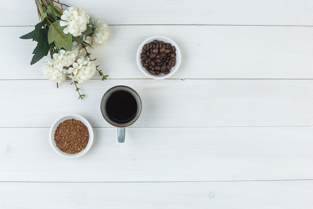 Top view coffee in cup with coffee beans, flowers, grinded coffee on wooden background. horizontal