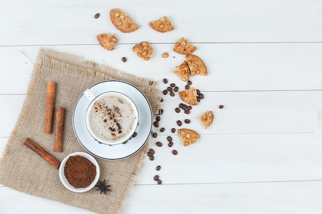 Top view coffee in cup with coffee beans, grinded coffee, cookies, cinnamon sticks on wooden and piece of sack background. horizontal