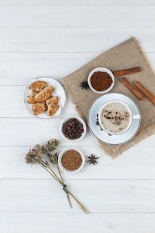 Top view coffee in cup with coffee beans, grinded coffee, spices, cookies, dried herbs on wooden and piece of sack background. vertical