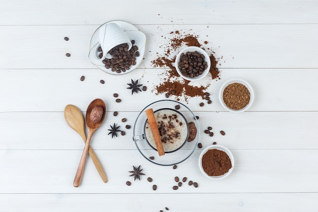 Top view coffee in cup with coffee beans, grinded coffee, spices, dates, wooden spoons on wooden background.