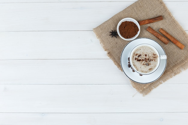 Top view coffee in cup with coffee beans, grinded coffee, spices on wooden and piece of sack background. horizontal