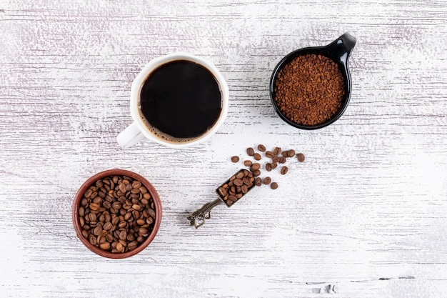 Top view coffee cup with coffee beans and instant coffee on white table