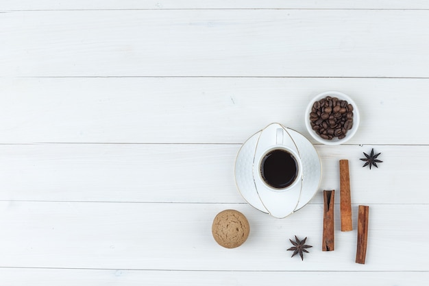 Top view coffee in cup with coffee beans, spices, biscuit on wooden background. horizontal