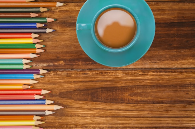 Top view of coffee cup with colored pencils