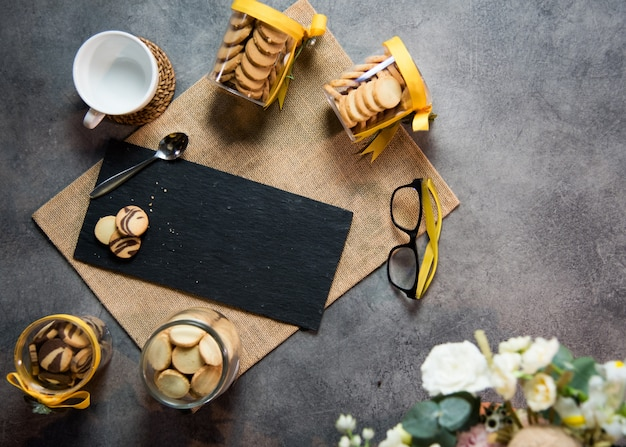 Top view coffee cup with cookies and black marble surface