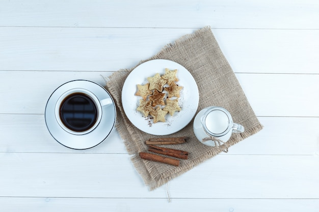 Top view coffee in cup with cookies, cinnamon sticks, milk on wooden and piece of sack background.