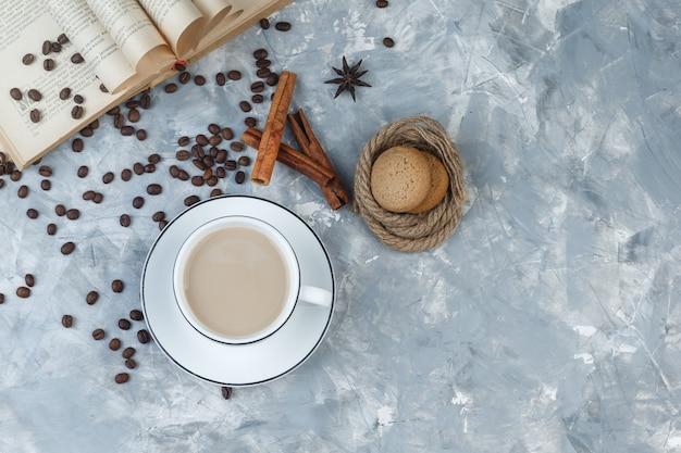 Vista dall'alto caffè in tazza con biscotti, chicchi di caffè, libro, spezie su sfondo grigio intonaco. orizzontale