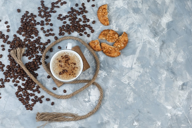 Top view coffee in cup with cookies, coffee beans, rope on grey plaster and wood piece background. horizontal