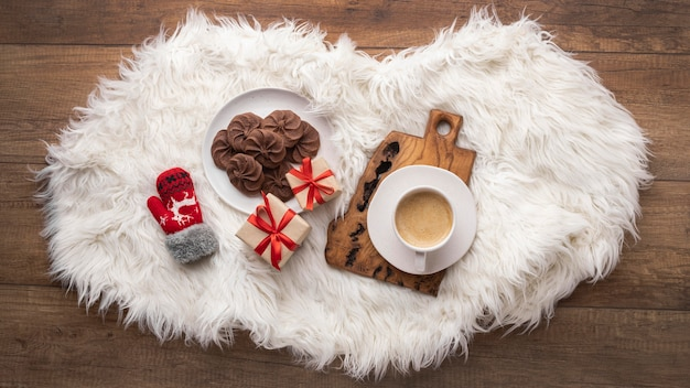 Top view of coffee cup with cookies and presents