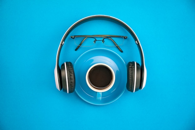 Top view of coffee cup with headphone and teacher glasses