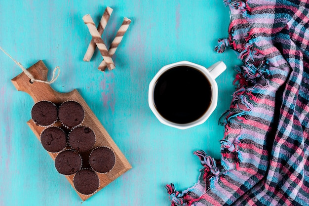 Top view coffee cup with muffins on wooden board on blue surface