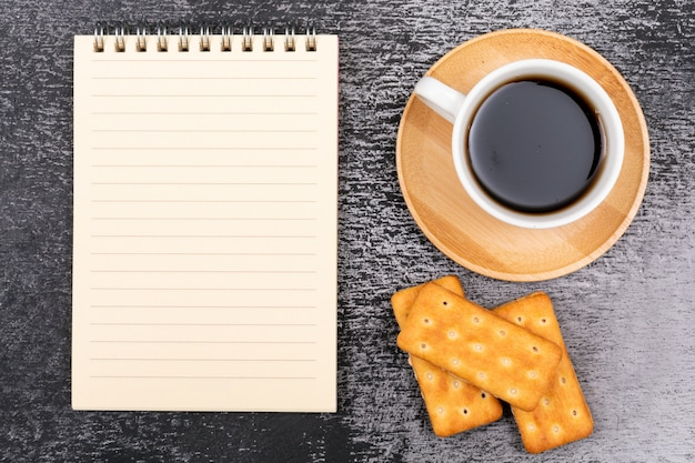 Top view coffee cup with notebook and cookies on dark surface