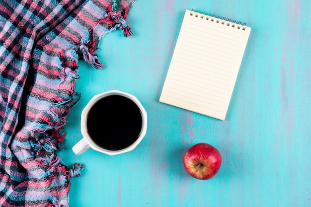 Top view coffee cup with notebook and red apple on blue table