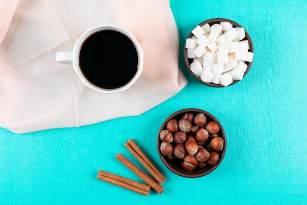 Top view coffee cup with sugar cubes cinnamon and nuts on green surface