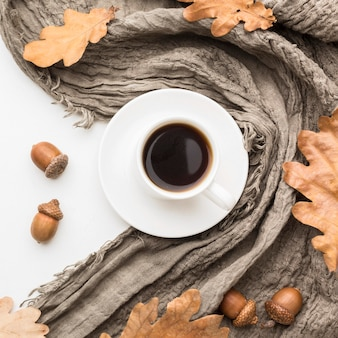 Top view of coffee cup with textile and autumn leaves