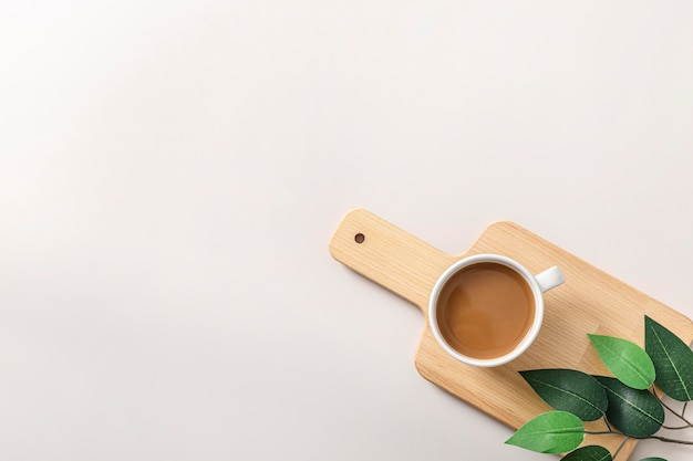 Top view of coffee cup on wooden chopping board with copy space