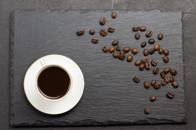 Top view of coffee drink in white cup and grains of coffee on a black table