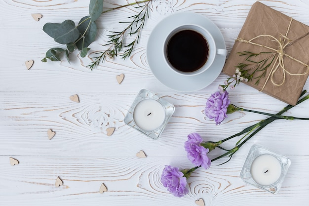 Top view of coffee, gift, candles, flowers on white wooden table.