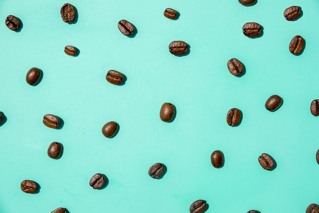 Top view coffee grains on green background