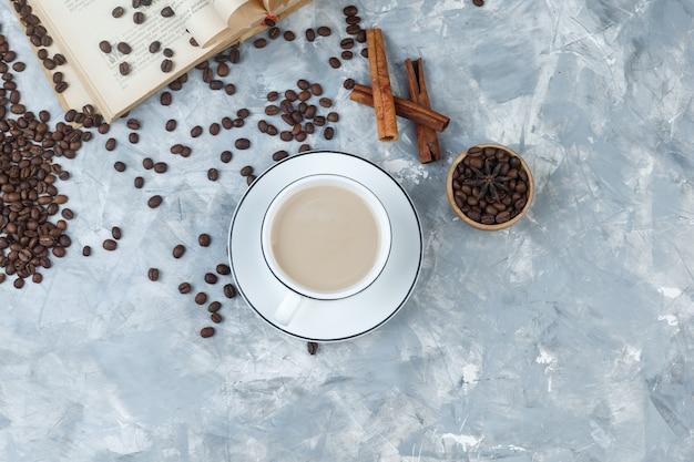灰色の漆喰の背景にコーヒー豆、本、シナモンスティックとカップのトップビューコーヒー。水平