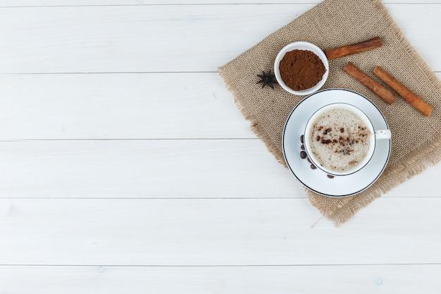 Вид сверху кофе в чашке с кофейными зернами, молотый кофе, специи на деревянном фоне и кусок мешка. горизонтальный