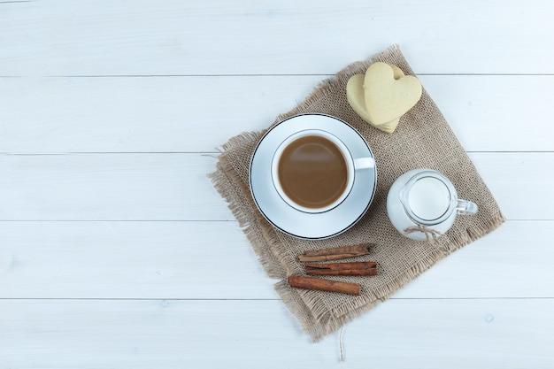 Вид сверху кофе в чашке с печеньем, палочками корицы, молоком на деревянном и куске фона мешка.