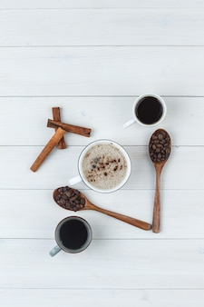 Вид сверху кофе в чашках с кофейными зернами, палочками корицы на деревянных фоне. вертикальный
