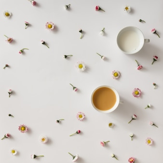 Top view of coffee and milk on white surface with colorful flower pattern
