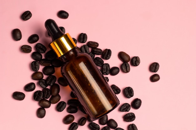 Top view coffee oil brown glass bottle and coffee beans mess pink pastel background