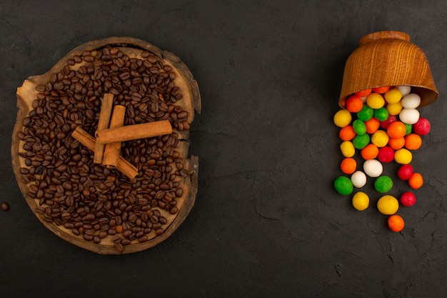 暗闇の中でシナモンと色とりどりのキャンディーと共にトップビューコーヒーの種子