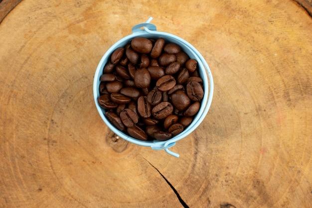 木製の机の上の青い鍋の中に茶色のトップビューコーヒー種子