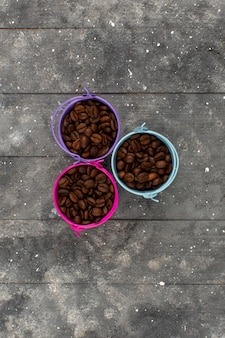 Вид сверху кофейные зерна коричневые целые внутри разноцветных горшочков на сером деревенском деревянном полу