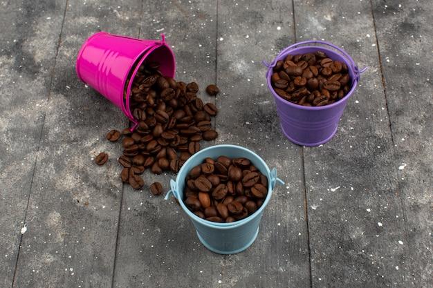 Vista dall'alto semi di caffè marrone intero all'interno di vasi multicolori sul grigio rustico in legno