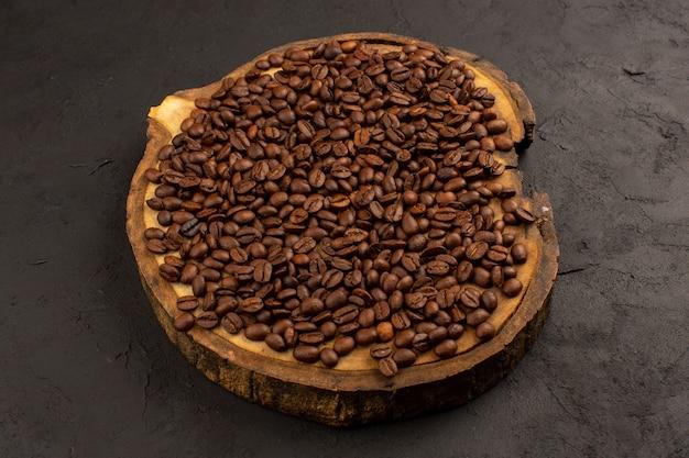 茶色の机と暗い床に茶色の全体のコーヒー豆の上面図