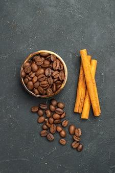 Вид сверху семена кофе в миске с палочками корицы на темном изолированном фоне