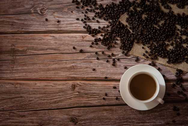 Top view of coffee in white cup and coffee beans on wooden background with copy space